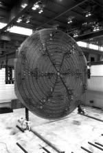 [Photo of the cyclotron vacuum tank being lowered onto the magnet.]
